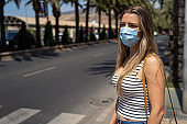 woman with face mask walking around the city during the coronavirus pandemic