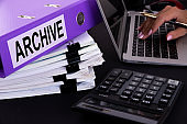 Text, word ARCHIVE is written on a folder lying on documents on an office desk with a laptop and a calculator. Business concept.