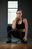 A young, beautiful, athletic girl does exercises with a Pilates ring in the gym. Sports Slavic girl in a black suit. Copy space, gray background, sport banner for advertising