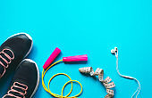 Fitness sport equipment and accessories on blue background flat lay with copy space workout