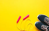 Jump rope and sports shoes on yellow background.Minimalist fitness concept. Top view and copy space flat lay.