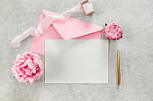 Mockup invitation, blank paper greeting card, pink envelope and peonies on gray stone table. Flower background. Flat lay, top view