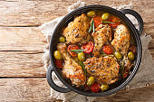 Delicious chopped chicken baked with green olives, tomatoes and onions, herbs close-up in a frying pan. horizontal top view