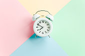 White alarm clock on colorful background. Trendy minimal style. Beauty and fashion concept. Flat lay composition. Top view