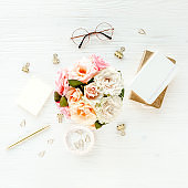 Women's workspace with pink and beige roses flowers bouquet, accessories, diary, glasses on white background. Flat lay, top view. Beauty blog concept
