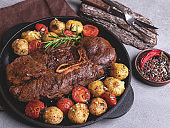 grilled beef steak with bone, roasted new potatoes  tomato with garlic in a pan