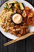 Japanese hibachi lunch made of fried rice, shrimp, steak and vegetables close-up on the table. Vertical top view