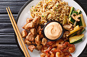 Full hibachi dish with rice, shrimp, steak and vegetables served with sauce closeup in a plate. Horizontal top view