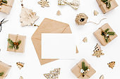 Styled desk with envelope, blank card, craft boxes and Christmas decorations. Flat lay. Mockup template. View from above