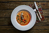 Italian cuisine. Plate of tomato risotto, olive oil and cherry tomatoes on wooden background
