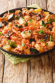 Spicy rice with chicken, zucchini and mushrooms in tomato sauce close-up in a frying pan. vertical