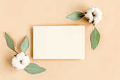 Mockup invitation, blank greeting card and green leaves eucalyptus. Flat lay, top view