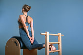 Beautiful positive blond woman is being prepared performing pilates exercise, training on barrel equipment. Fitness concept, special fitness equipment, healthy lifestyle, plastic. Copy space, sport banner for advertising