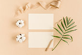 Mockup invitation, blank greeting card and tropical palm leaves. Flat lay, top view