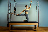 leotard workout pilates training. athletic pilates reformer exercises. pilates machine equipment. young woman pilates stretching sport in reformer bed instructor girl in a studio
