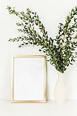 Blank frame mockup with a branches of eucalyptus in vase on table on light background. Home decor. Blog, website or social media concept