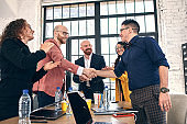 Business handshake at meeting or negotiation in the office. Partners are satisfied because signing contract or financial papers. selective focus
