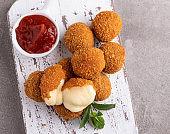 Fried breaded mozzarella cheese balls with tomato sauce