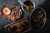 Assorted meat after cooking is laid out on a plate. Set for serving meat dishes. view from above