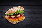 Appetizing sandwich on a wooden board. Baguette sandwich with filling from lettuce, slices tomato. Dark wooden background. View from above. Close-up. Macro photography