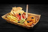 fast food and unhealthy eating concept - close up of french fries, pita and shrimp, tomato and guacamole sauce on paper box