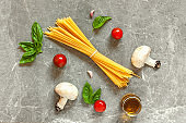 Top view of ingredients for pasta with mushrooms: spaghetti, basil, garlic,cherry and olive oil on gray stone background