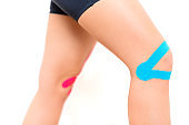 Studio shot of a female patient with kinesio tape on her knee, isolated over white. Kinesiology, physical therapy, rehabilitation background. Cropped shot close up.