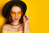 Beauty Model with orange professional look accessories. Fashion woman with long, straight hair. Trend make up. Orange background. Girl in a big black hat and yellow sunglasses. Empty copy space