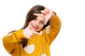 Adorable elementary age girl smiling while looking at camera and making photo frame hand gesture. Studio shot on white background.