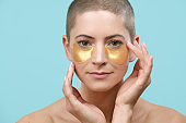 Attractive young woman applying gold collagen eye mask. Photo of mid adult caucasian woman with shaved head and healthy skin isolated on pastel blue background. Beauty products concept.
