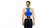 Rear view three quarter length studio shot of a female patient with tape on her neck and lower back, isolated over white background.