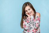 Adorable young smiling girl with attitude. Cheeky child waist up portrait on pastel coloured blue background.