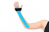 Close up studio shot of a female arm with tape, isolated over white background.physical therapy, rehabilitation concept.