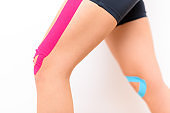Studio shot of a female patient with tape on her knee, isolated over white. Physical therapy, rehabilitation background. Cropped shot close up.