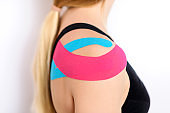 Studio shot of a female patient with tape on her shoulder and back, isolated over white.Physical therapy, rehabilitation background.
