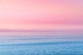 Cotton candy sky and blue calm sea.