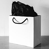 Black and white image of paper gift bag with a black rope handles on wooden table.
