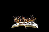 The crown of thorns lies on the open book of the Bible. Objects on an isolated black background.