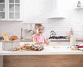 A cute little girl is cooking homemade cakes in the kitchen.