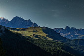 Starry night over Italian alps. Mountains in the moonlight.