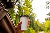 Young woman holds a disposable cup of coffee on on a sunny morning or day.