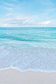 Bali beach scene - turquoise Indian ocean, white sand and blue sky on the background.
