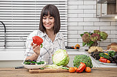 Young beautiful woman preparing fresh vegetable salad. Healthy food and diet concept.
