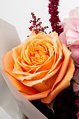 Beautiful bouquet with soft pink Hydrangea (Hydrangea macrophylla) or Hortensia flower, mild orange roses and red wrapping paper.