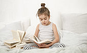 Cute little girl reading a book on the bed in the bedroom.