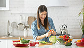 A young woman is preparing a salad in the kitchen .