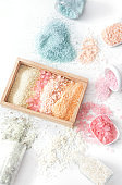 Composition with multi colored sea salt on a white background.
