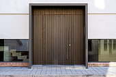 Massive wooden entrance door to modern white house with paving footpath in the city.