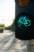 Traffic lights for bicycles on a sunny summer day with blurred city view in a background.
