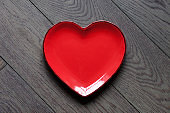 A red heart shape plate on dark wooden background.